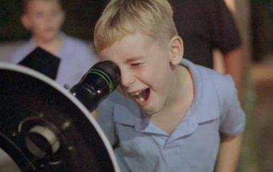 Një burrë dërgon teleskopin në rrugë, njerëzit shikojnë hënën