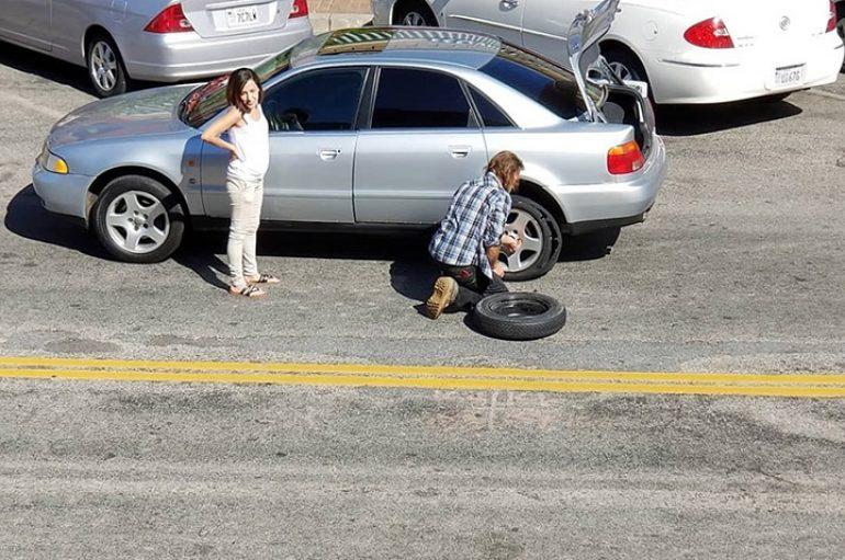 I pastrehu i ndërron gomën e makinës një gruaje